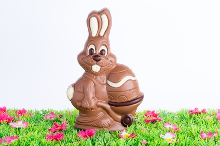 Easter bunny made of chocolate with easter egg on a green meadow with flowers isolated on a white background
