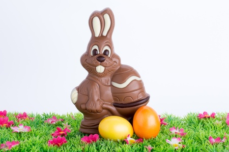 Easter bunny made of chocolate with colorful easter eggs on a green meadow with flowers isolated on a white background