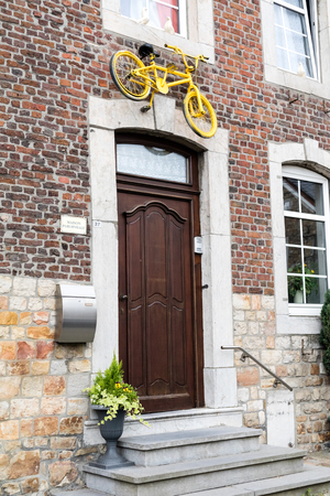 HENRI-CHAPELLE, BELGIUM, 25th JUNE, 2017 - painted bike fixed on a house wall