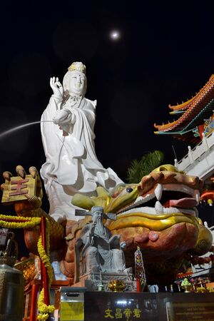 Guan Yin Statue On Night Time With Crescent Moon Of Thailand Southeast Asia