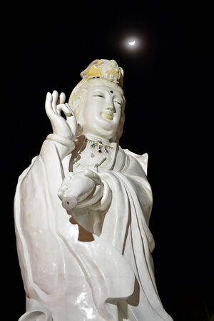 Guan Yin Statue On Night Time With Crescent Moon Of Thailand Southeast Asia photo