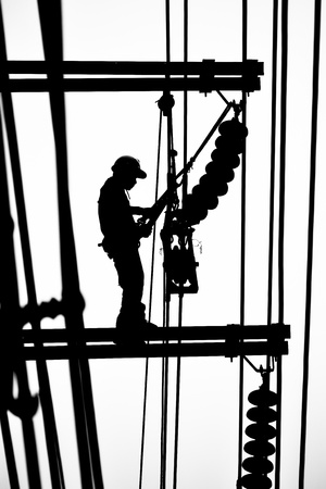 silhouette electrician working on electricity post