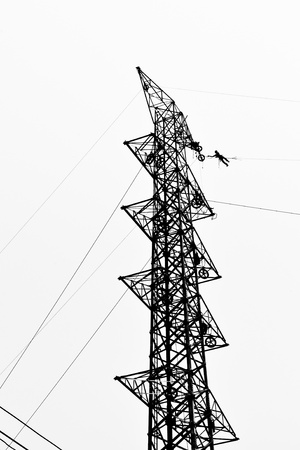 silhouette electrician working on electricity tower post photo