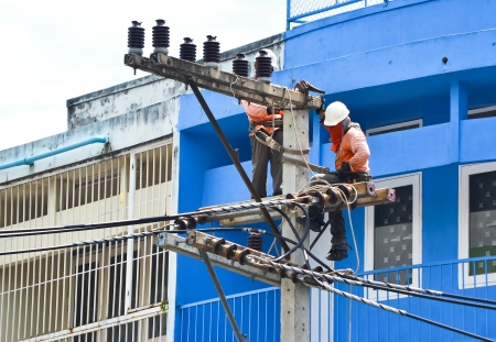 dangerous man: electrician working on electricity post