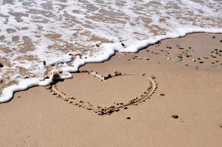 hart vorm in het zand uitgehold door de zee Stockfoto