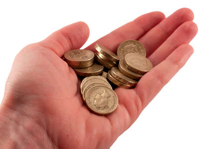 coinage: A female hand holding several british pound coins