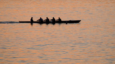 Rowers against sea at sunset photo