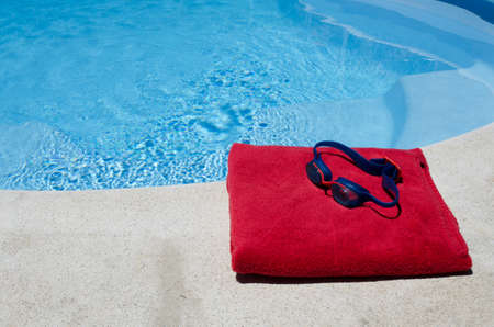 swimming goggles: Swimming goggles and towel by side of pool Stock Photo