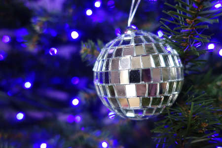 christmas tree ball: Silver ball hanging on a Christmas tree with blue lights in the background
