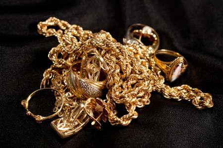 joyas de oro de chatarra incluyendo cadenas, pulseras y anillos en un fondo negro