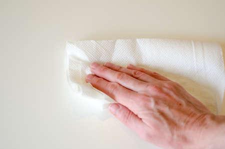 Hand wischt weißen Tisch mit weißen Küchenpapier