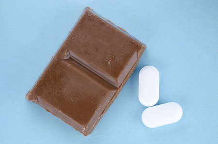 analgesics: Chocolate triggers migraine headaches concept with piece of chocolate and two painkiller tablets Stock Photo