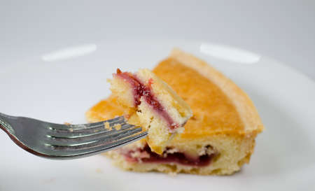 mouthful: Mouthful of bakewell tart on fork with slice in background