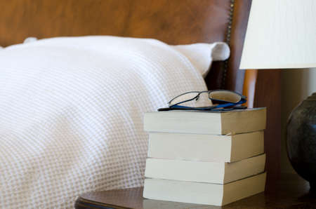 bedside: Pile on books with reading glasses on bedside table