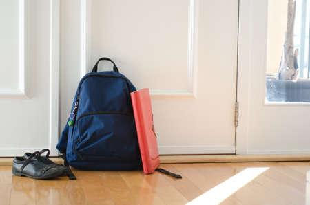 zapatos escolares: Volver a la escuela o listos para concepto de escuela con mochila y los zapatos por la puerta delantera