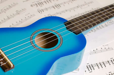 sheet music: Blue guitar on a background of sheet music
