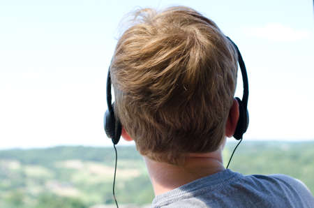 Boy with headphones on a bright summers day Stock Photo