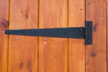 hinge: Metal hinge on a wooden door