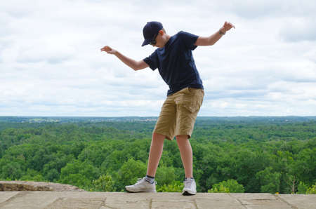 Junge balanciert am Rande eines Tropfen - Gefahrenkonzepts Standard-Bild