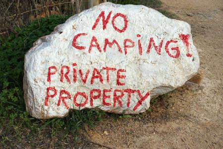 大きな白い岩に赤で書かれた私有財産の看板