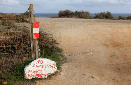 Private Property sign written in red on large white rock Standard-Bild