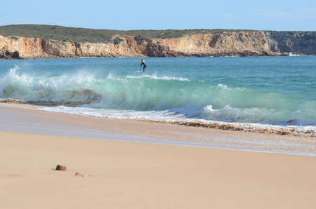 Beach with paddle boarder surfing waves Standard-Bild