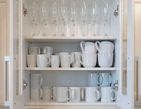 Cupboard full of white mugs and champagne glasses
