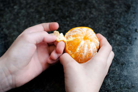 Childs hands peeling a tangerine Stock Photo