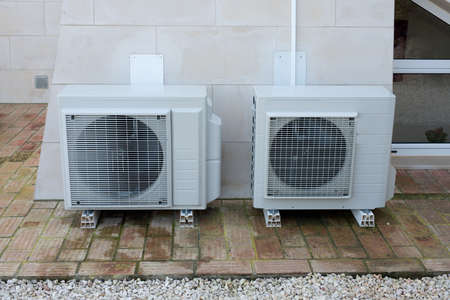 Two air conditioning units outside a house