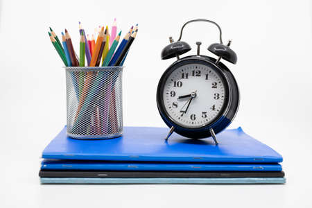 Time for school concept with books, pencils and alarm clock