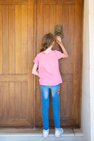 young girl knocking on front door of house using metal door knocker Imagens