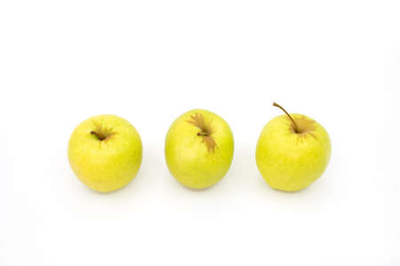 Three yellow apples in a row on a white Stockfoto