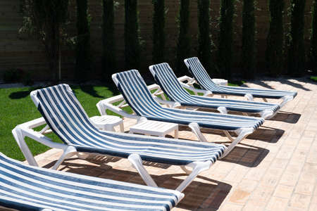 Row of stripy blue and white sunbeds in the sun