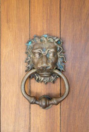 Antique metal door knocker in the shape of a lions head