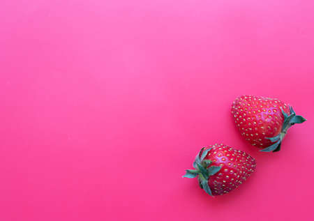 Two strawberries on a pink