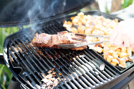 Steak and potato chunks cooking on a outdoor grill Stockfoto