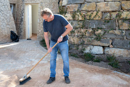 Man sweeping up gravel on his drive way with a broom Stockfoto