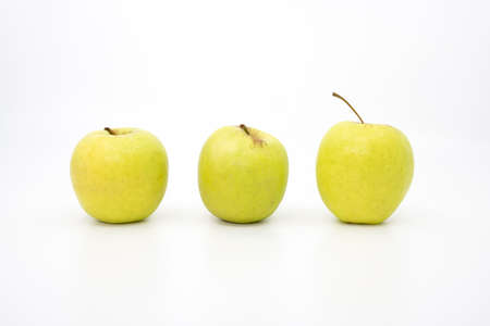 Three green apples in a row on a white