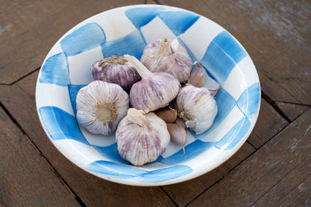 Ceramic bowl full of whole garlic bulbs on a wooden table Stockfoto