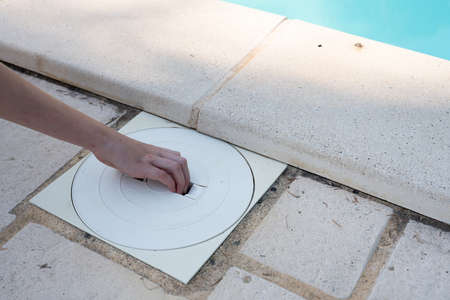hand removing the lid from a pool skimmer basket