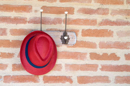 Red hat hanging on a coat hook against a brick wall background Stockfoto