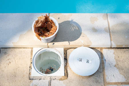 Removing a pool skimmer basket to empty the leaves out