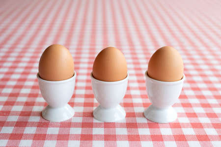 Three boiled eggs in egg cups in a row on a table