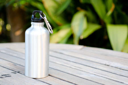 Reusable water bottle on a wooden table outdoors