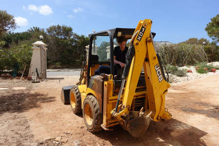 Algarve, Portugal 10 April 2019: A JCB mini digger being used to do landscaping work in a front garden