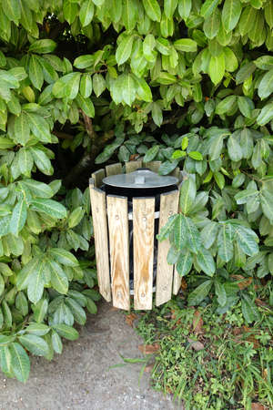 rubbish bin in a park in front of a hedge