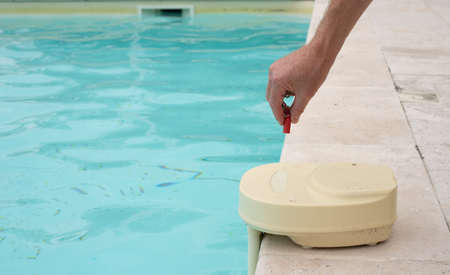 mans hand with contact key used to deactivate swimming pool alarm Standard-Bild
