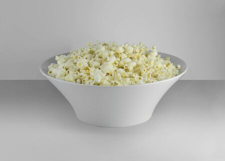 Popcorn on the plate. Isolated on clean natural background. Good for while watching cinema and movies. Delicious but unhealty nutrition. Side view.