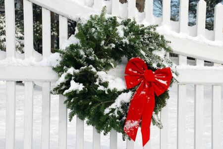 fence: Christmas Wreath on Fence with Snow Stock Photo