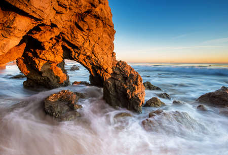 Beautiful golden cave and rocks at the El Matador Beach, Malibu at sunset time photo